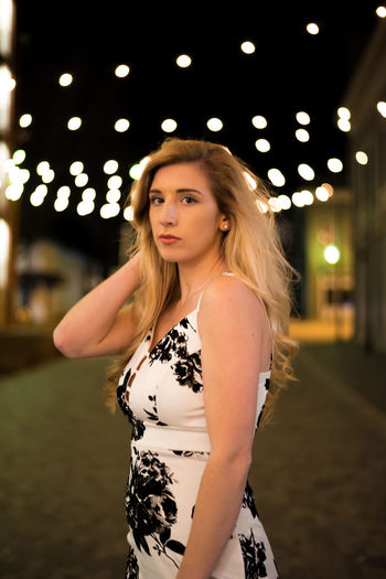 Portrait of young woman against illuminated lights