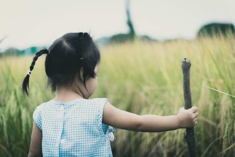 Rear view of girl holding stick while standing on field