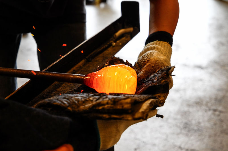 Craftsperson holding blowpipe with molten glass at workshop