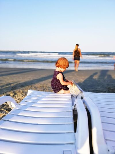 Girl sitting on lounge chair with mother in background at beach