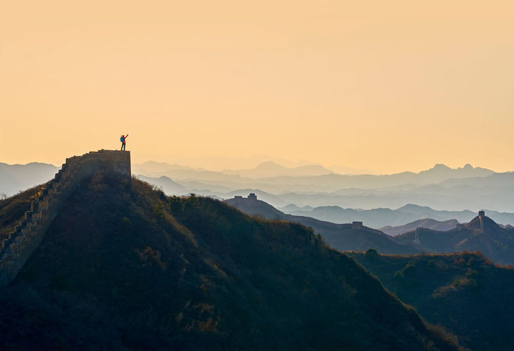 Person on great wall of china at mountain during sunset