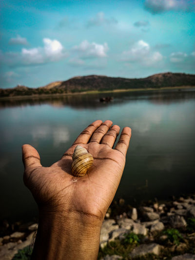 Close-up of human hand against lake