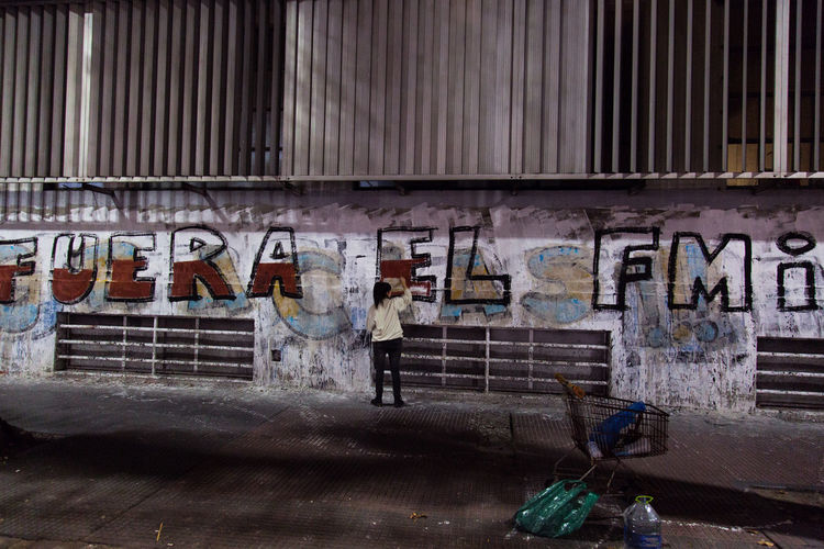 Buenos Aires, Argentina A woman paints a wall with a slogan against the International Monetary Fund Buenos Aires FMI IMF Against Argentina Art And Craft Built Structure Corruption Crisis Damaged Demonstration Famulari Financial Graffiti Money Wall Wall - Building Feature