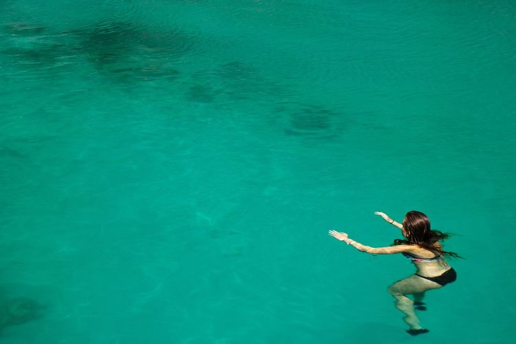 Aerial view on women swimming alone in turquoise water