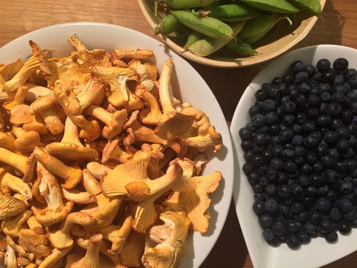 Close-up of green peas with mushrooms and blueberries in bowl