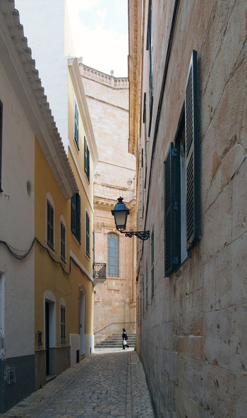 a woman walking past the end of a long quiet alley in cuitadella menorca with old historic buildings and the steps of the old cathedral in visible in the distance Ciutadella Street Alley Menorca Architecture Building Exterior Built Structure Building Window Residential District Narrow City Day Direction Lighting Equipment No People The Way Forward Outdoors Footpath Low Angle View Electric Lamp Sky