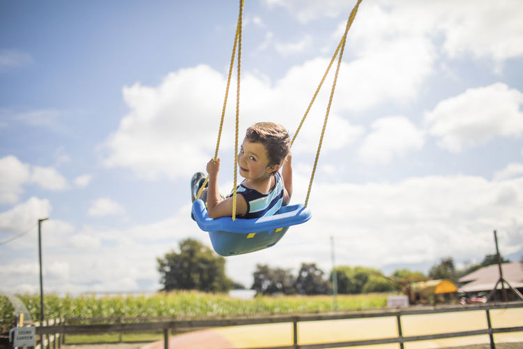 Low angle view of girl on swing against sky