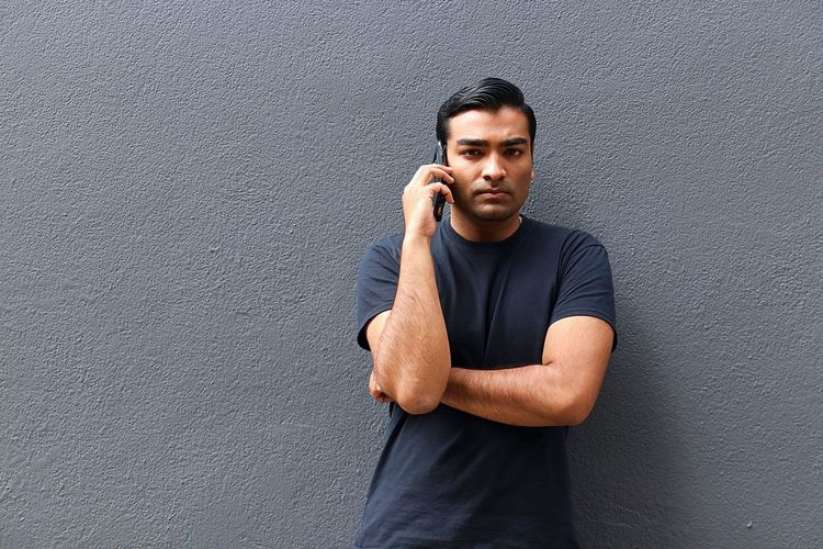 Young handsome man on smart phone making a call while standing against a grey wall Angry Black Blue Jeans Call Cellphone Conversation Eyebrow Grey Hairstyle Handsome Indian Outdoors Phone Phone Call Portrait Sad Smart Phone Smartphone Smile T Shirt Tech Technology Telephone Wireless Technology Young Man