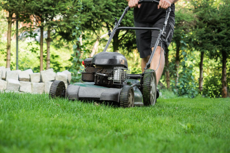 Low section of man mowing lawn