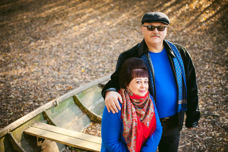 Portrait of mature couple by boat in forest during autumn
