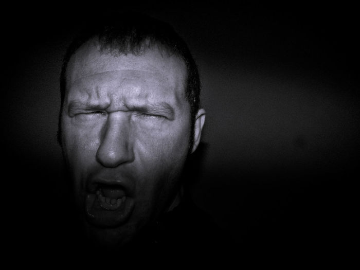 Close-up of angry blind man against black background