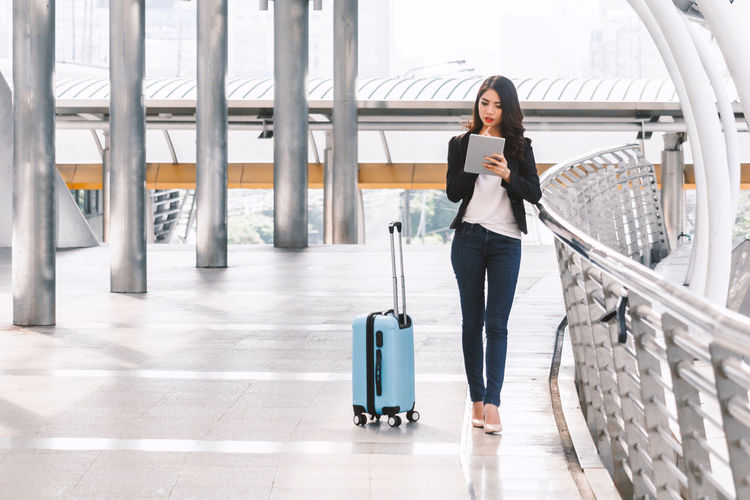 Happy successful businesswoman using a digital tablet computer Wireless Technology Full Length Communication Luggage One Person Technology Travel Holding Mobile Phone Using Phone Connection Suitcase Telephone Young Adult Front View Adult Airport Portability Journey Answering Outdoors Receiving