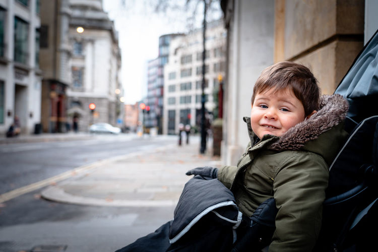 Baby boy sitting on his buggy and smiling Childhood Portrait One Person Child Looking At Camera Innocence Smiling Warm Clothing Outdoors Boys Clothing