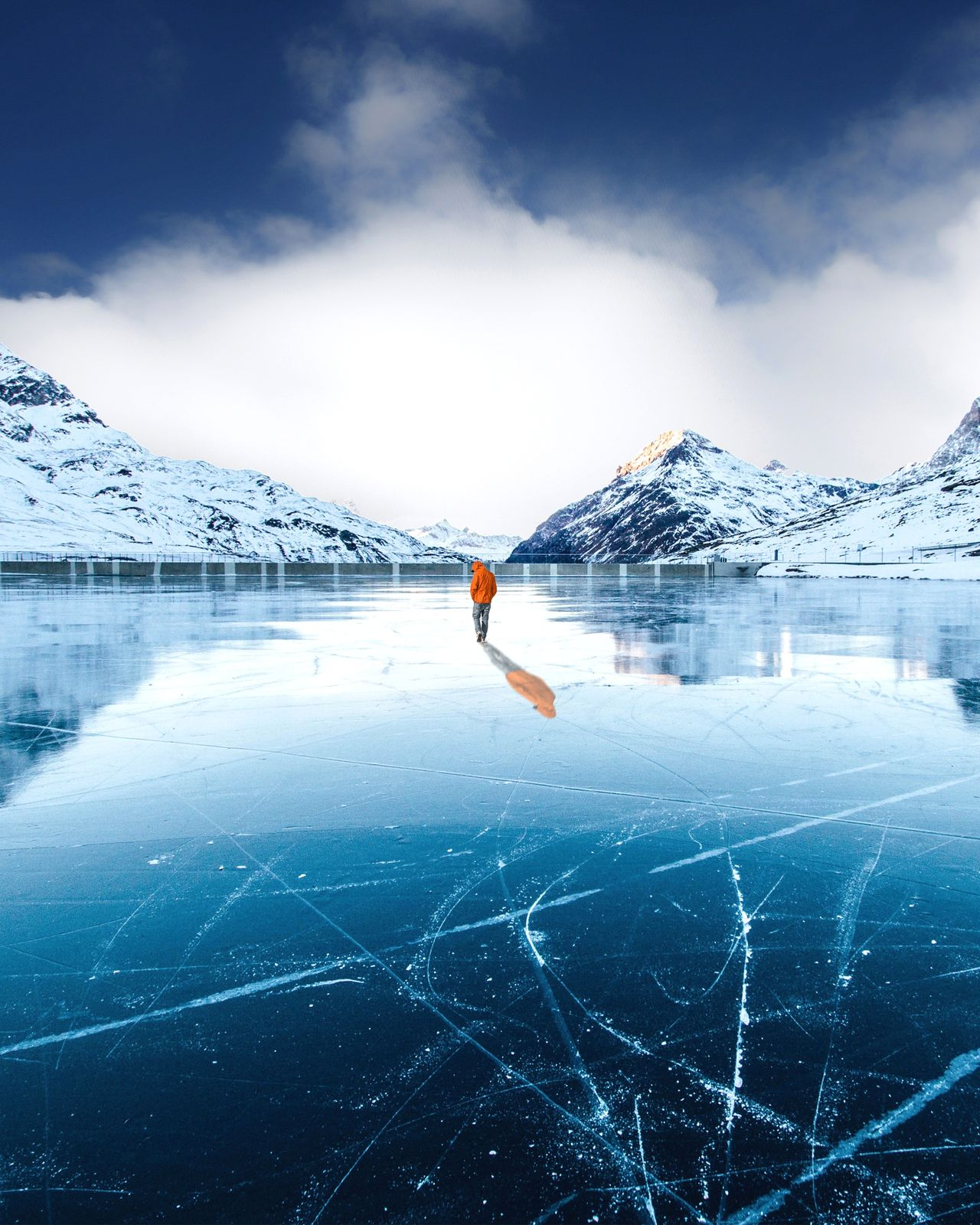 Man standing by frozen lake against mountain during winter