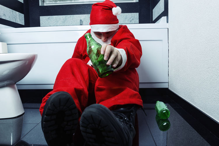 drunken santa claus sleeping at bathroom with beer bottle in hand and try to stand up Drunk Drunken Alcohol Beer Beer Bottle Stand Up Hangover Santa Claus Santa Sitting Try Again Celebration Christmas Party Holding Bottle Males  Clothing Bathroom Xmas