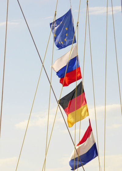 Low Angle View Of National Flags On Rope Against Sky