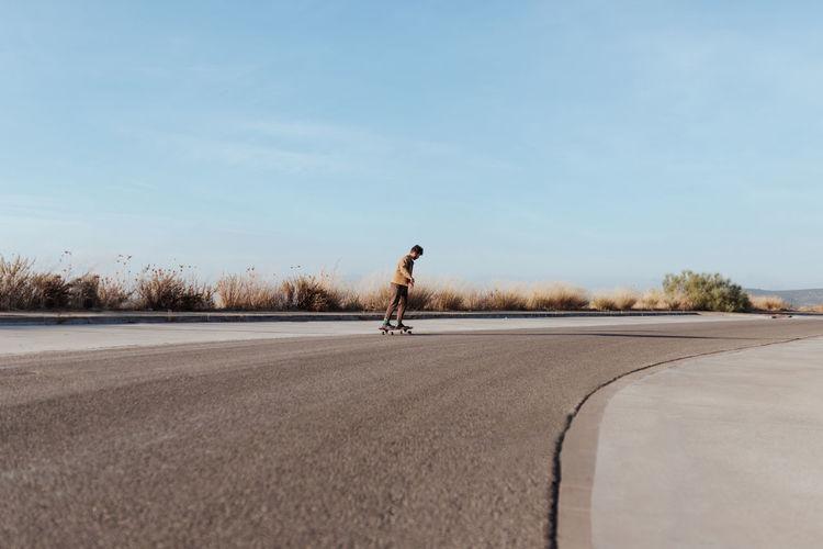 Man skateboarding on road against sky