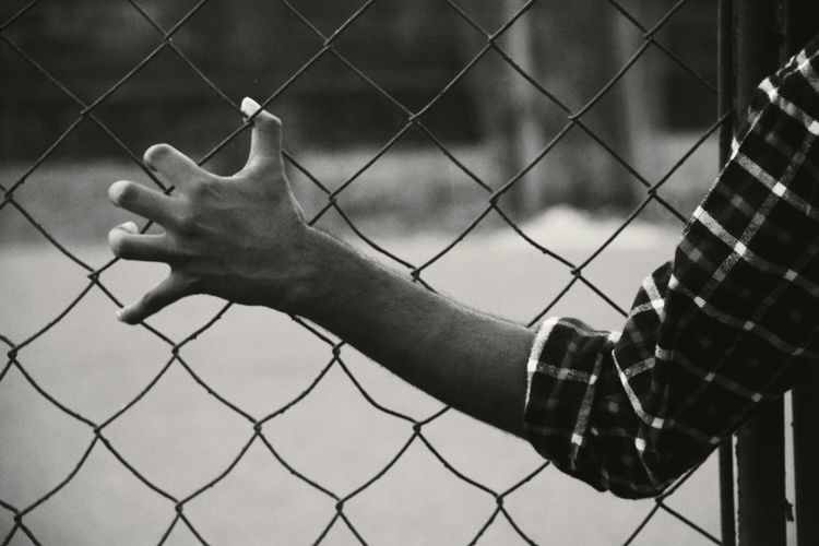 Close-up of man touching chainlink fence