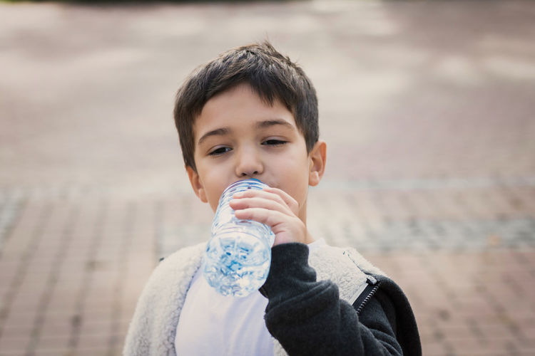 Boy Drinking Water From Bottle On Footpath