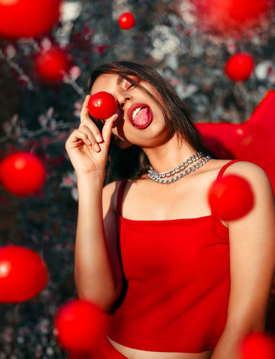 young woman holding a tomato