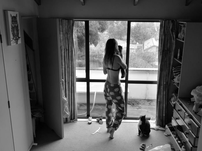 Full Length Rear View Of Woman With Cats Looking Through Window During Monsoon