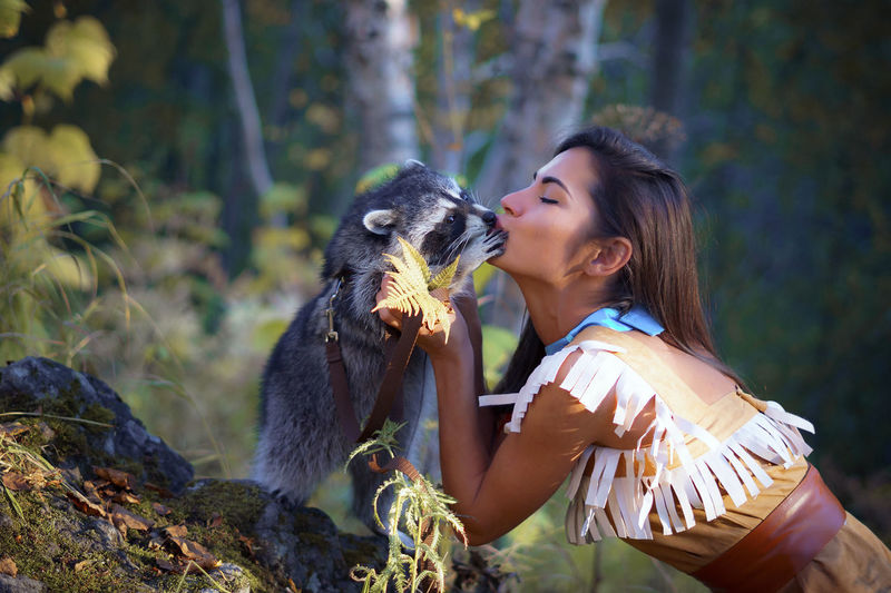 Side View Of Young Woman In Traditional Clothing Kissing Raccoon In Forest