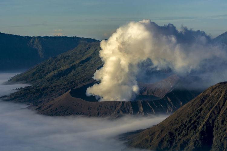 Aerial view of volcano emitting smoke against sky
