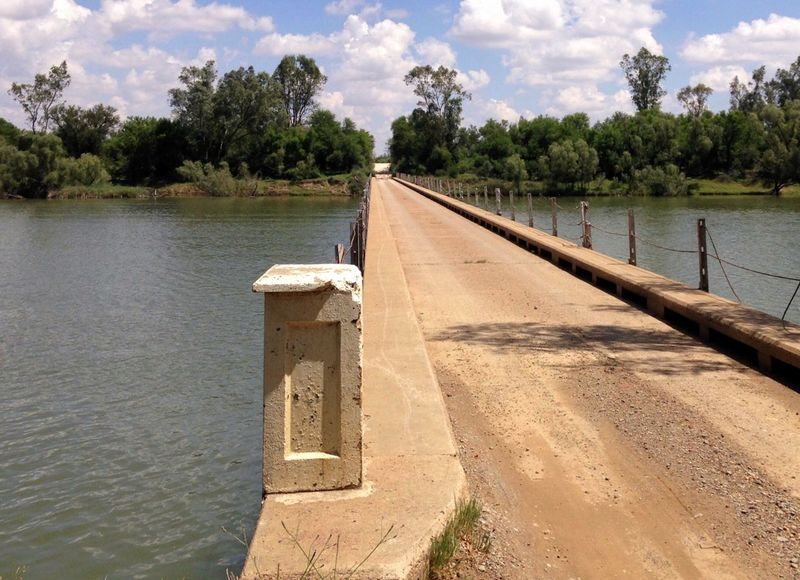 Concrete bridge over flowing river. Bridge Concrete River Tree Water Sky Outdoors Rust No People Day One Lane Bridge One Lane