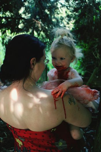 Mother holding daughter with blood on field