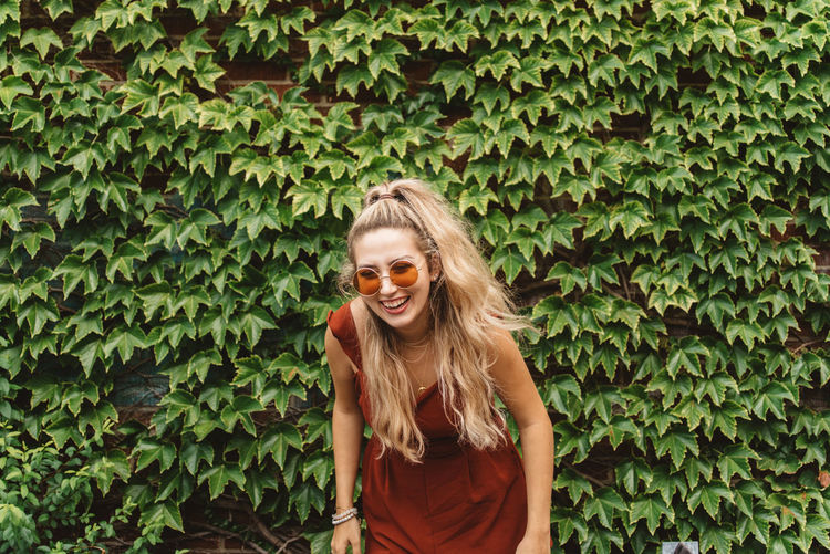 Cheerful young woman wearing sunglasses while standing against plants