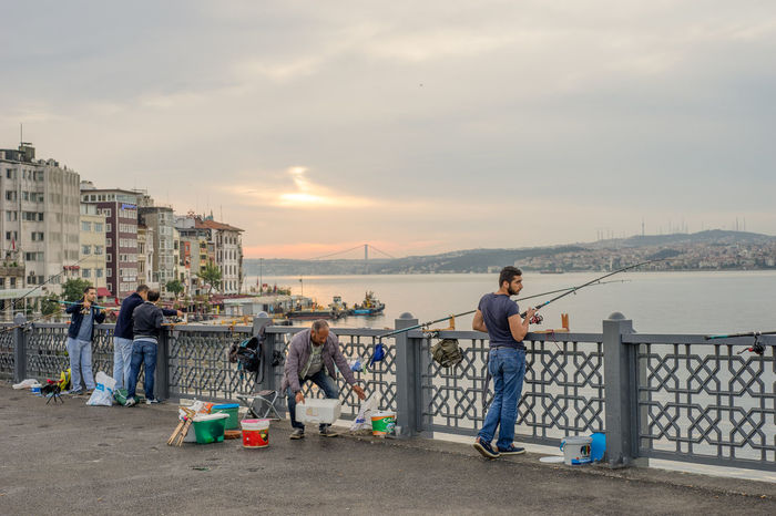 Istanbul, Turkey - Jun 28, 2015: Four men were fishing, facing Bosphorus Strait when sunlight just broke clouds in early morning, on Galata Bridge. One man was also selling fishing gears. Bosphorus Clouds Culture Daybreak Fishing Fishing Rods Galata Bridge Handsome Hobby Istanbul Lifestyle Many Monochrome Morning People Sea Sell Sky Strait Travel Turkey Visiting