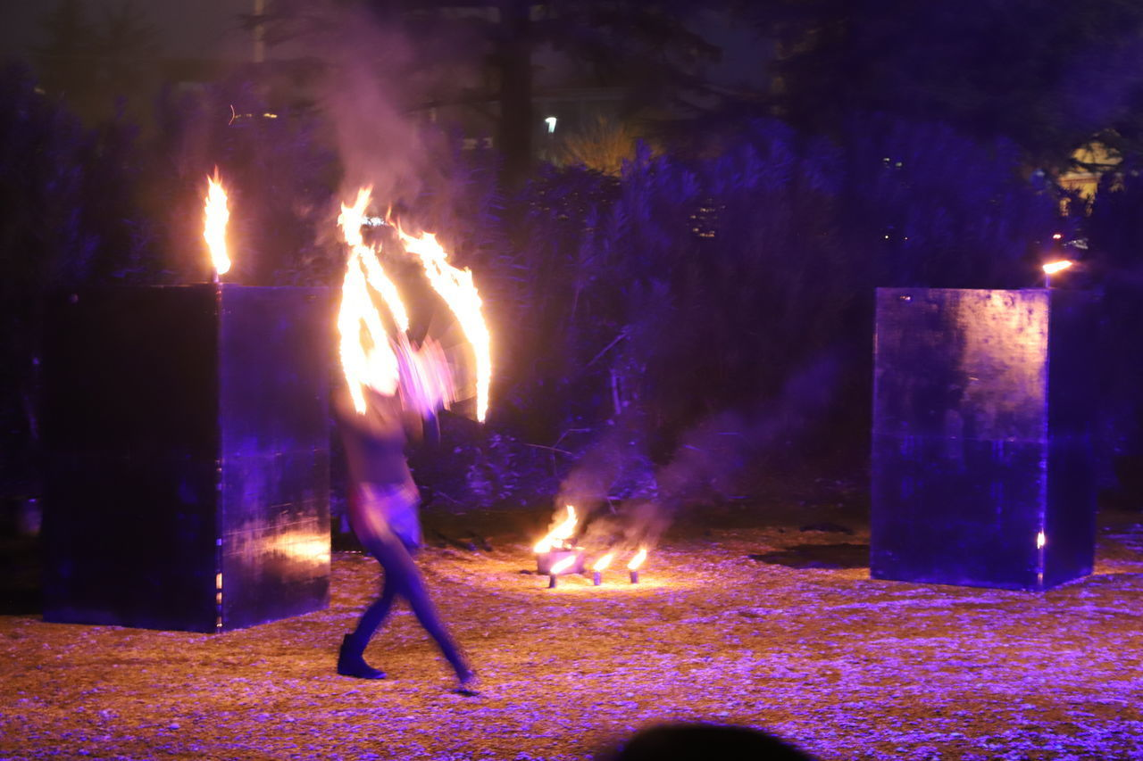 flame, burning, fire, heat - temperature, real people, fire - natural phenomenon, night, motion, glowing, illuminated, long exposure, nature, one person, blurred motion, lifestyles, celebration, full length, men, leisure activity, outdoors