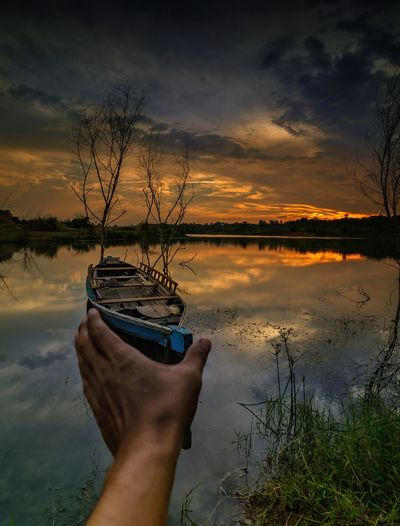 Optical illusion of hand holding rowboat in lake during sunset