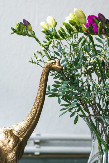 Golden dinosaur eating my flowers Dinosaur Funny Humor Lifestyle Animal Close-up Day Diplodocus Docoration Flowers Fugure Gold Colored Green Color Hipster Indoors  Interior Leaf Model No People Pink Color Plant Plastic Still Life Toy