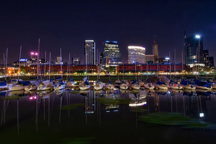 Boats moored on lake against city at night