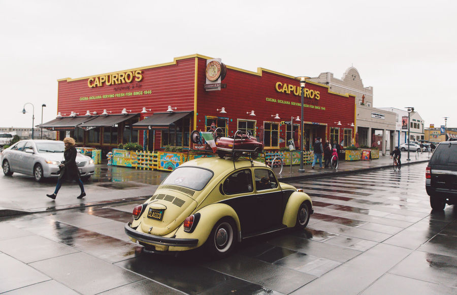 Architecture Beetle Building Exterior Built Structure Car City City Life Clear Sky Communication Curly Hair Day Full Length Girl Land Vehicle Lifestyles Men Mode Of Transport Outdoors Rainy Day Real People Text Transportation Travel Visit Western Script
