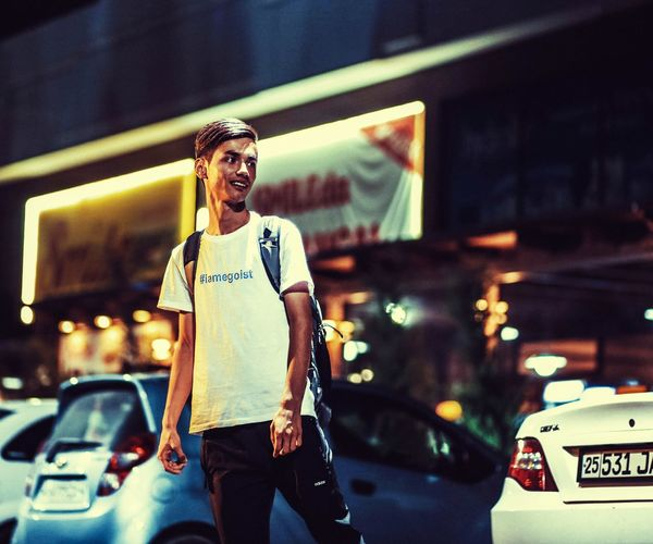 Young man standing by car in city