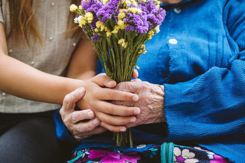 Grandparents day, reunited family, togetherness. senior old grandma hugs granddaughter outdoors