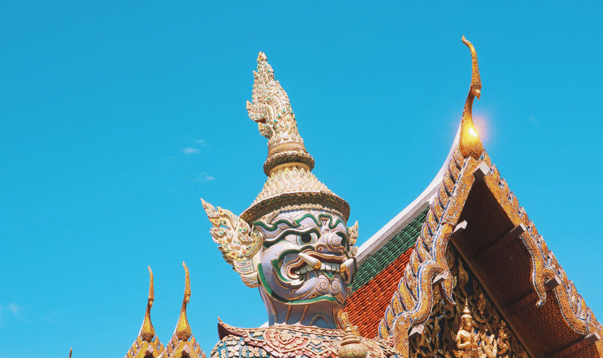 Low angle view of temple against building against clear blue sky and a demon statue in bangkok