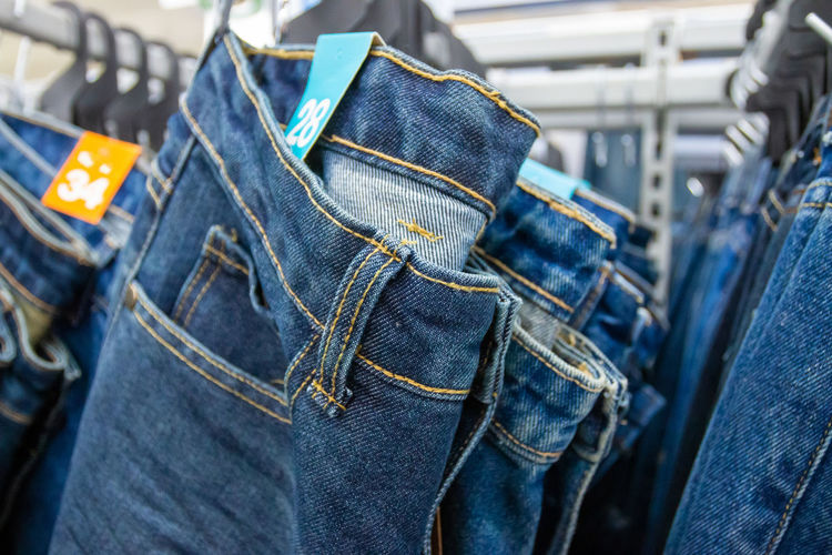 Close-up of jeans hanging in store for sale