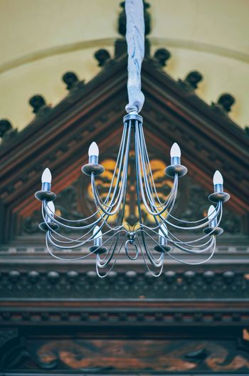 Low angle view of electric lamp hanging on ceiling at home