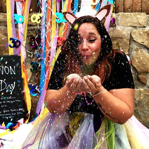 Woman blowing confetti at party