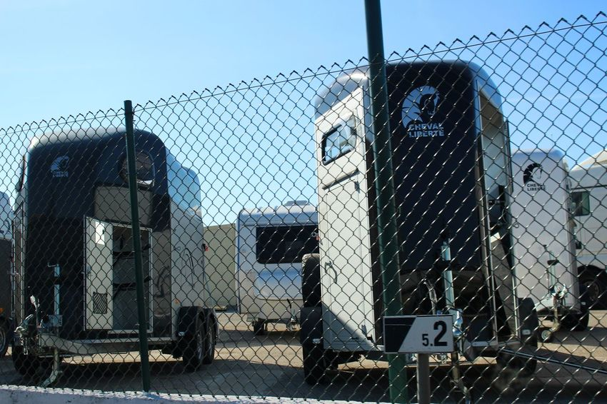 Clear Sky Low Angle View Parking Lot Sunlight Transportation Blue Blue Sky Close-up Day Detail Equipment Fence Horse Trailer Metal Mode Of Transport No People Number Outdoors Parking Protection Safety Sky Stationary Street Trailer