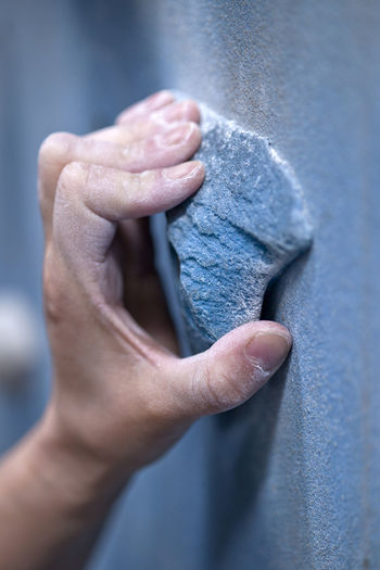Close-up of man hand against wall
