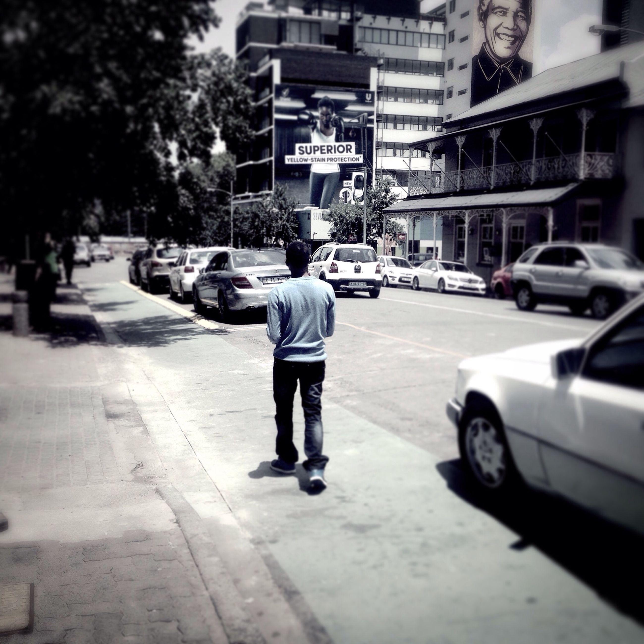 street, car, transportation, walking, rear view, building exterior, city, road, full length, land vehicle, city life, lifestyles, mode of transport, architecture, men, city street, built structure, sidewalk