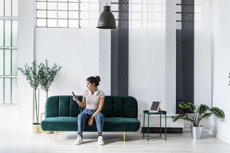 Full length of woman sitting on sofa
