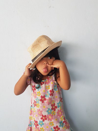 Girl wearing hat against wall