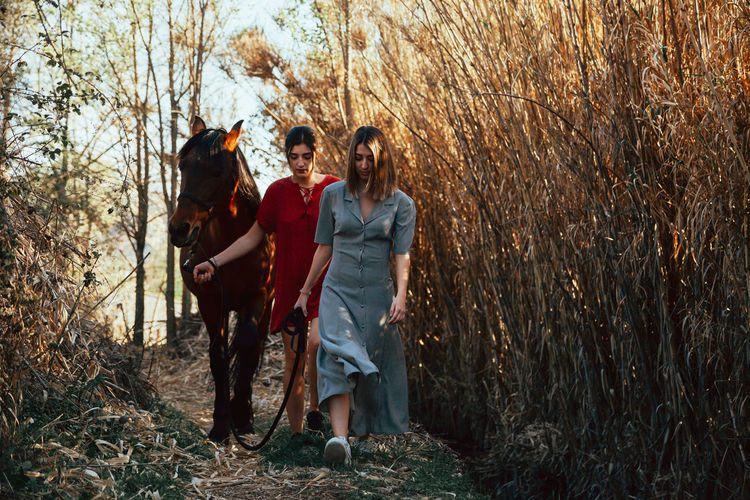 Young women walking with horse amidst plants