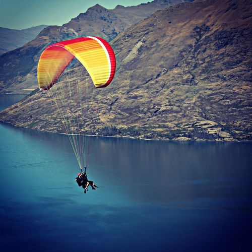 People paragliding over sea and against rocky mountain