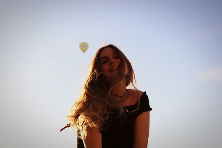 Low angle view of smiling young woman against hot air balloon